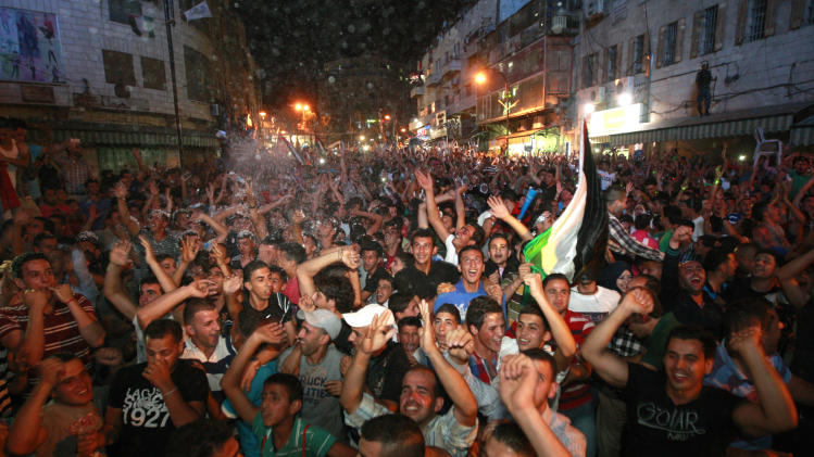 "Palestinians celebrate after Palestinian singer Mohammed Assaf won a regional TV singing contest, in the West Bank city of Ramallah, Saturday, June 22, 2013. Palestinians relished a rare moment of pride and national unity Saturday after the 23-year-old wedding singer from a refugee camp in the Gaza Strip won ""Arab Idol,"" a regional TV singing contest watched by millions of people. (AP Photo/Majdi Mohammed)"