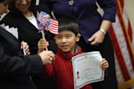 Born in China, Zachary Shields, 6, holds up his citizenship certificate during a 2011 citizenship ceremony in Fairfax, Virginia. Asians recently passed Hispanics as the largest group of new immigrants to the United States, according to a survey predicting a demographic trend bringing powerful economic, social and political changes