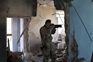 Toshifumi Fujimoto takes pictures inside a heavily damaged apartment in Aleppo on December 30, 2012. Fujimoto's passion has taken him from the dull routine of the highway to Syria, where as part of his latest adventure in the Middle East's hot spots he shoots photos and video while dodging bullets with zest