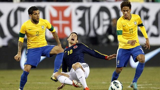 Brazil's Daniel Alves (L) tackles Colombia's James Rodriguez (C) as Brazil's Neymar looks on (Reuters)