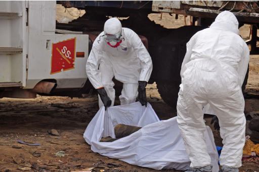 The body of a man found in the street, suspected of dying from the ebola virus is covered and removed by health workers, in the capital city of Monrovia, Liberia, Tuesday, Aug. 12, 2014. The World Health Organization declared it's ethical to use untested drugs and vaccines in the ongoing Ebola outbreak in West Africa although the tiny supply of one experimental drug handed out to three people has been depleted and it could be many months until more is available. (AP Photo/Abbas Dulleh)