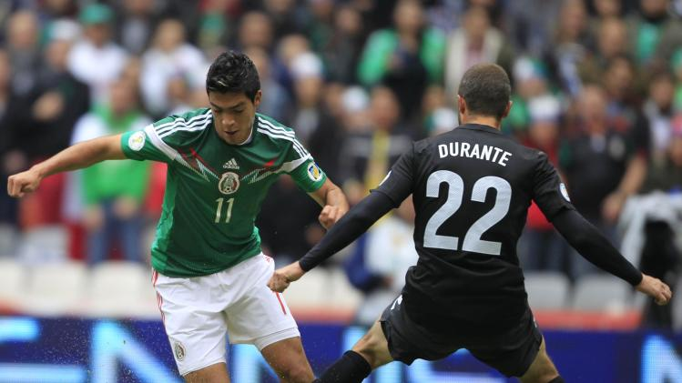Raul Jimenez of Mexico battles for the ball against Andrew Durante of New Zealand during their World Cup qualifying playoff first leg soccer match at the Azteca stadium in Mexico City