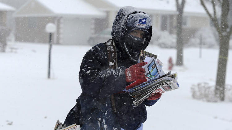 Arlington Heights, Ill.  mail carrier Tequilia Brock endures the wet heavy snow as a winter storm moves through the Northwest suburbs of Chicago on Tuesday, Feb. 26, 2013. (AP Photo/Daily Herald, Mark Welsh) MANDATORY CREDIT; MAGS OUT; TV OUT