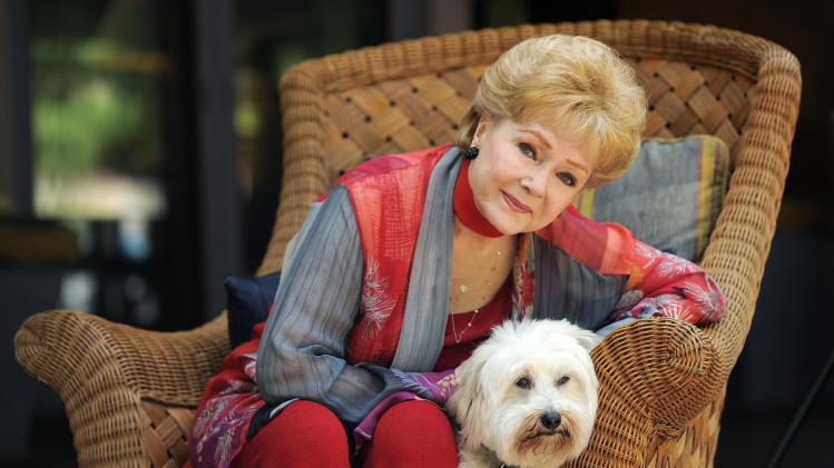 "In this Tuesday, May 21, 2013 photo, Debbie Reynolds, a cast member in the film ""Behind the Candelabra,"" poses for a portrait with her dog, Dwight, in Beverly Hills, Calif. Reynolds plays Frances, the mother of the pianist and vocalist, Liberace. HBO debuts ""Behind the Candelabra"" in the US, Sunday, May 26, 2013. (Photo by Chris Pizzello/Invision/AP)"