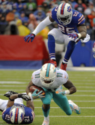 Miami Dolphins wide receiver Mike Wallace (11) is pursued by Buffalo Bills defenders Leodis McKelvin (21) and Da'Norris Searcy (25) during the first half of an NFL football game Sunday, Dec. 22, 2013, in Orchard Park, N.Y. (AP Photo/Gary Wiepert)