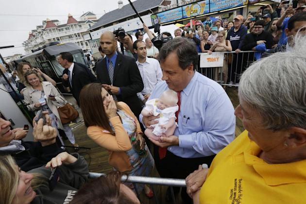 New Jersey Gov. Chris Christie, right, holds 6-week-old Willow DeParre, as first lady Mary Pat Christie looks on as they greet people during the opening of the New Jersey shore, Friday, May 24, 2013,