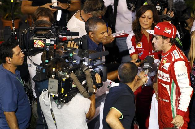 Ferrari Formula One driver Alonso is interviewed after the qualifying session of the Singapore F1 Grand Prix in Singapore