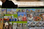 Calendars showing Pope Benedict XVI (C) and John Paul II are displayed in a newstand on February 15, 2013 in Rome. Benedict's decision to step down for age reasons has revealed tensions at the heart of the Church, emphasised by a battle between top cardinals over whose candidate should be appointed to head up the Vatican's scandal-hit bank