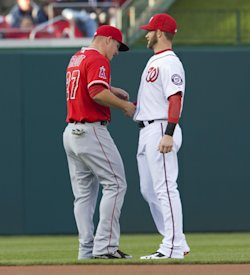 Mike Trout (left) and Bryce Harper shake hands before a game last season. (AP)