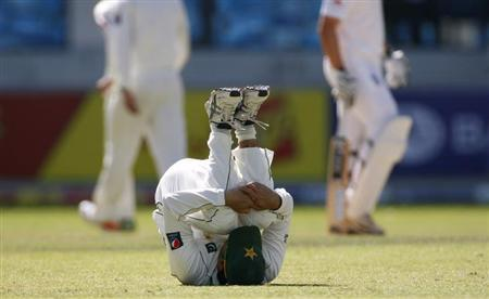 Pakistan's Ajmal stretches during the first cricket test match against England at the Dubai International cricket stadium in the United Arab Emirates