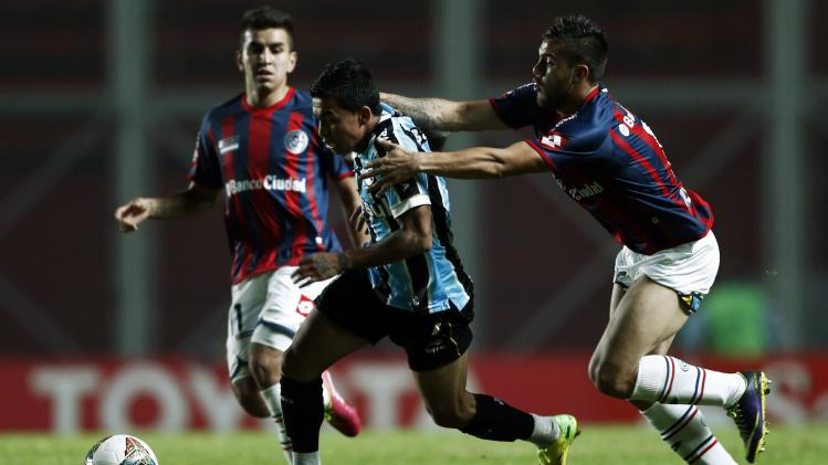 Villalba of Argentina's San Lorenzo tries to stop Dudu of Brazil's Gremio during their Copa Libertadores soccer match in Buenos Aires