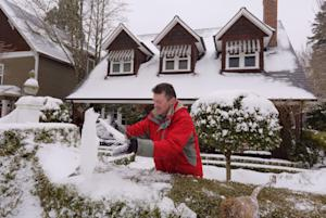 Shaun Burke cleans the ice and snow off the English…