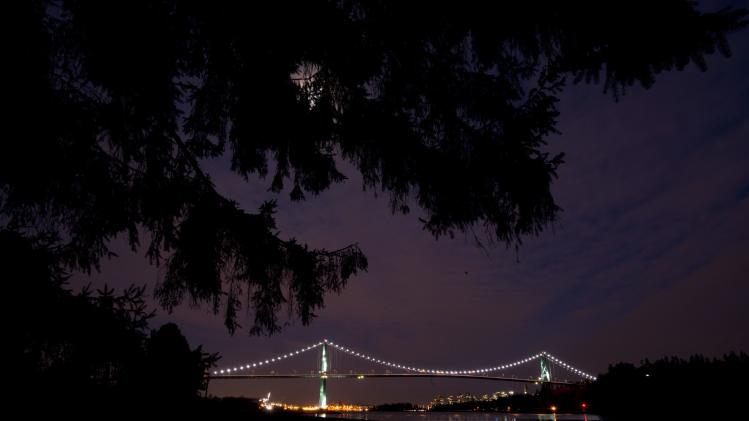 The lights on the Lions Gate bridge are on prior to Earth Hour as seen from West Vancouver, British Columbia, Saturday, March 23, 2013. (AP Photo/The Canadian Press, Jonathan Hayward)