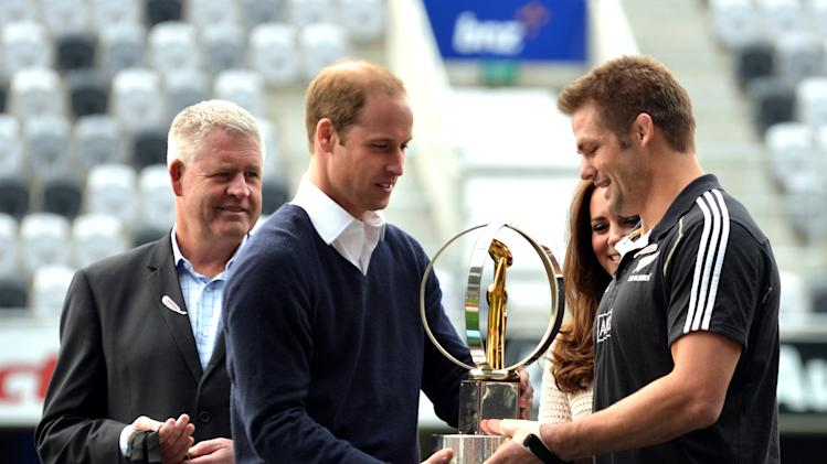 Britain's Prince William, second from left, presents the IRB World Trophy to All Blacks rugby captain Richie McCaw, right, watched by Kate, Duchess of Cambridge, second right, and New Zealand Rugby Union's CEO Steve Tew, in Dunedin, New Zealand, Sunday, April 13, 2014. The royal couple are on an official visit to New Zealand. (AP Photo/Peter Mcintosh, Pool)
