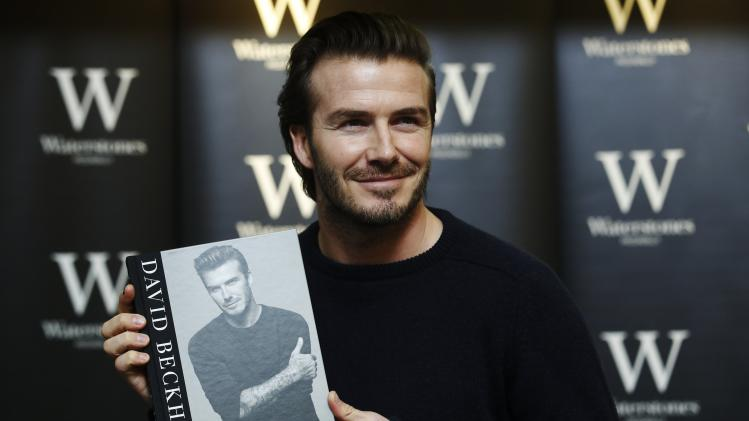 "Retired soccer player David Beckham poses with his book ""David Beckham"" at a bookshop in London"