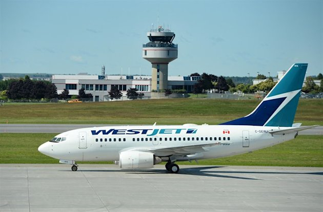 A WestJet aircraft is pictured on the tarmac in Ottawa on Thursday. The airline has suffered a rash of threats over the past week, grounding several flights and affecting travel for passengers. THE CANADIAN PRESS/Sean Kilpatrick