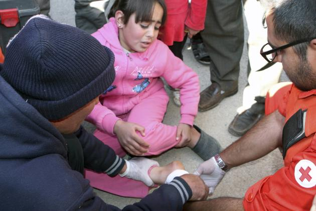 File photo of Lebanese Red Cross members attending to a wounded girl in Tfail village near the Syrian border
