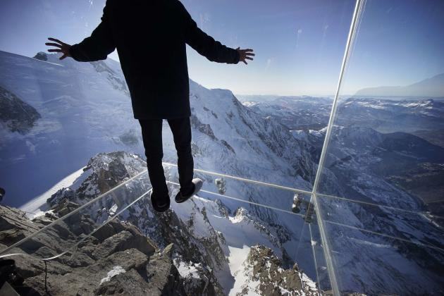 A journalist, wearing slippers to protect the glass floor, stands in the 'Step into the Void' installation during a press visit at the Aiguille du Midi mountain peak above Chamonix, in the Fre