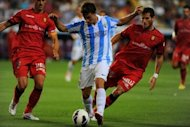 Mallorca's Tomer Hemed (R) and Jose Nunes (L) fight for the ball as Malaga's Sebastian Fernandez advances during their Spanish League match on August 25. Mallorca seized their opportunity with Hemed heading home an Emilio Unsue cross