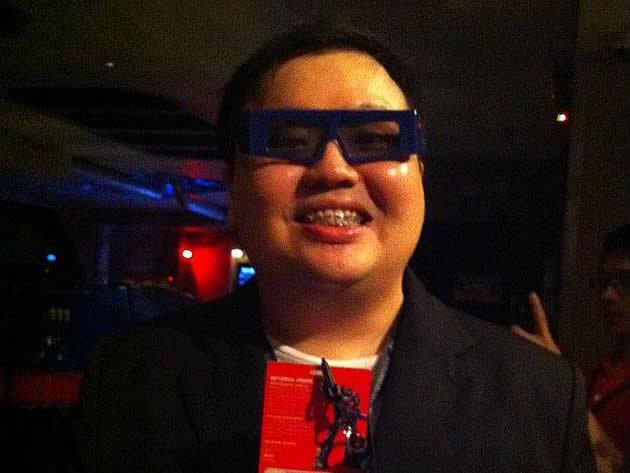 Transformers hardcore fan Marcus Goh wears his 3D glasses and holds up his VIP pass before boarding the Transformers ride. (Photo courtesy of Marcus Goh)
