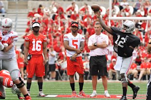 J.T. Barrett (16) and Braxton Miller (5) watch as Cardale Jones runs the offense. (Getty Images)