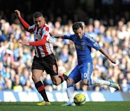 Chelsea's Spanish midfielder Juan Mata (right) shoots past Brentford's Harlee Dean to score the opening goal of the English FA Cup fourth round replay match in London on February 17, 2013. Chelsea eased into the fifth round with a 4-0 win
