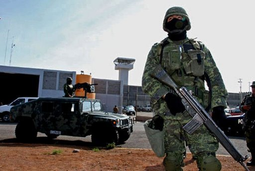 Mexican soldier stand guard outside the Piedras Negras federal prison where a group of prisoners escaped on September 18, 2012. The Mexican authorities are hunting for the 131 escaped inmates near the US border.