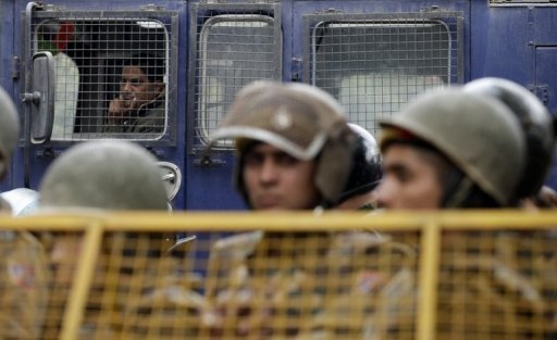 Police are seen watching protesters from behind a barrier during a rally in New Delhi, on December 30, 2012. Police on Tuesday arrested a man who was allegedly trying to plant a crude bomb near the home of one of the accused in the New Delhi gang-rape and murder case.