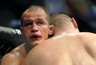 Junior dos Santos and Cain Velasquez grapple during their fight. (AP)