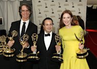 "From left, Director Jay Roach, writer Danny Strong, and Actress Julianne Moore, pose backstage with the awards they won for the HBO movie ""Game Change,"" at the 64th Primetime Emmy Awards at the Nokia Theatre on Sunday, Sept. 23, 2012, in Los Angeles. (Photo by Matt Sayles/Invision/AP)"