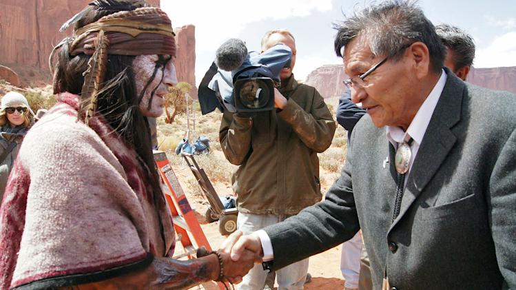 "This April 2012 photo released by the Navajo Nation shows, actor Johnny Depp shaking hands with Navajo Nation President Ben Shelly in Monument Valley during the filming of ""The Lone Ranger."" The Pendleton blanket was presented to Johnny Depp as a good will gesture on behalf of the Navajo Nation.  (AP Photo/Emerald Craig, Navajo Nation)"