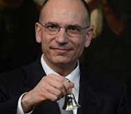 Newly-appointed Italian PM Enrico Letta rings a silver bell -- marking the start of his office -- before the start of his first cabinet meeting at Rome's Chigi Palace on April 28, 2013. Letta said his coalition government will act fast to reverse an austerity policy he argued was killing Italy and called on Europe to become a motor for growth