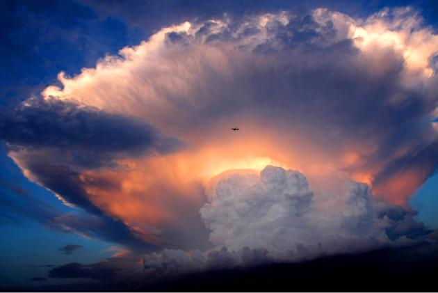 A jet plane flies past a mushroom-like cumulonimbus storm cloud in Beijing, China (REX)
