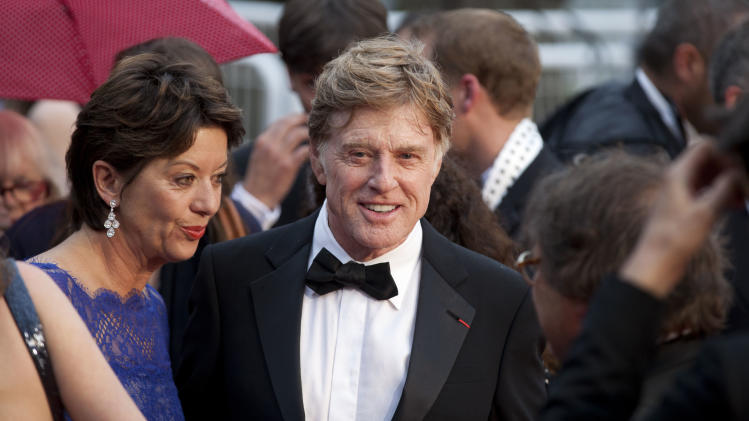 Actor Robert Redford, centre, and his wife Sibylle Szaggars, centre left, arrive for the screening of All Is Lost at the 66th international film festival, in Cannes, southern France, Wednesday, May 22, 2013. (AP Photo/Virginia Mayo)