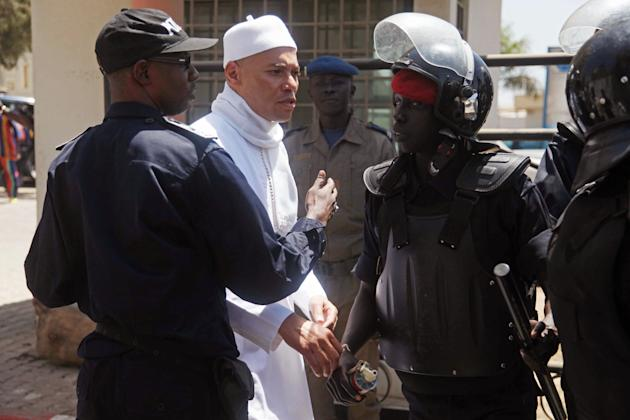 FILE - In this Friday, March 15, 2013 file photo, Karim Wade, center, the son of former Senegalese President Abdoulaye Wade, is blocked by police as he tries to approach journalists and gathered suppo