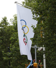 Workmen take down an Olympic flag in the Mall near Buckingham Palace in London, following the end of the 2012 Summer Olympics, Monday Aug. 13, 2012. The London summer games ended late Sunday, with the next summer games due in Rio de Janeiro, Brazil, in 2016. (AP Photo/Alastair Grant)