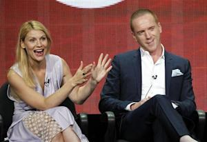 "Claire Danes gestures next to Damian Lewis at a panel for the television series ""Homeland"" during the Showtime portion of the Television Critics Association Summer press tour in Beverly Hills"