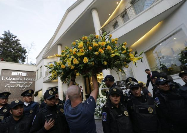 A man carries a flower wreath outside the funeral home where the body of Colombian Nobel Prize laureate Garcia Marquez was taken to, in Mexico City