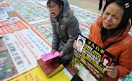 "File photo shows Chinese parents pleading for the return of their abducted children, as some 2,700 photos of missing children are laid out on a square in Fuzhou, southeast China's Fujian province. Human trafficking remains a serious problem in China, with many sociologists blaming the nation's ""one-child"" family planning policy for fuelling the crime"