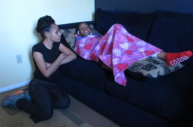 Shanita Miller sits in her Indianapolis apartment on Thursday, Feb. 5, 2015, next to her daughter Sinai. (AP)