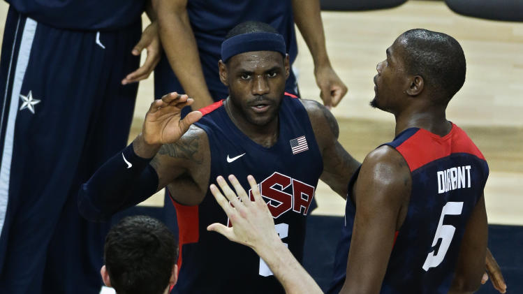 United States' Lebron James, center, is congratulated by teammates Kevin Durant, right, and Kevin Love, bottom, after slamming a dunk in a men's basketball semifinal game against Argentina at the 2012 Summer Olympics, Friday, Aug. 10, 2012, in London. (AP Photo/Victor R. Caivano)