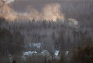Flames and smoke are seen at the site of a train derailment in Wapske, New Brunswick, January 8, 2014. REUTERS/Mathieu Belanger