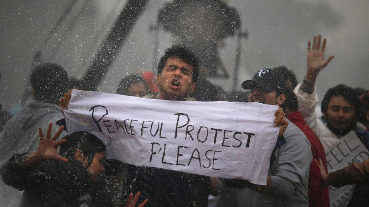 Protesters react as police officers use a water cannon to disperse them near the India Gate as they protest the gang rape and brutal beating of a 23-year-old student on a bus last week, in New Delhi, Sunday, Dec. 23, 2012. (AP Photo/ Saurabh Das)