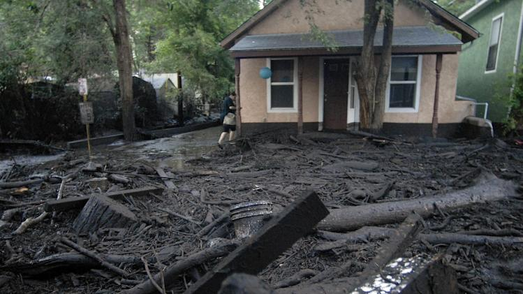 Fire-blackened debris from last year's Waldo Canyon Fire lies in front of a home in Manitou Springs, Colo. after a flood swept it down through a section of the historic Colorado town just west of Colorado Springs on Monday, July 1, 2013. The town is vulnerable to severe flooding after the foothills just west of the town were burned. (AP Photo/Bryan Oller)