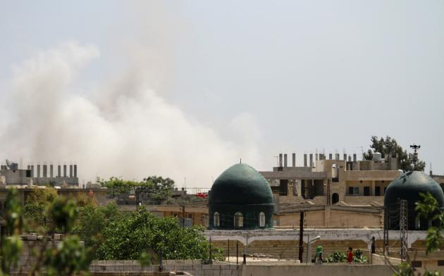 Smoke rises after the dropping of a barrel bomb in Kafarzita