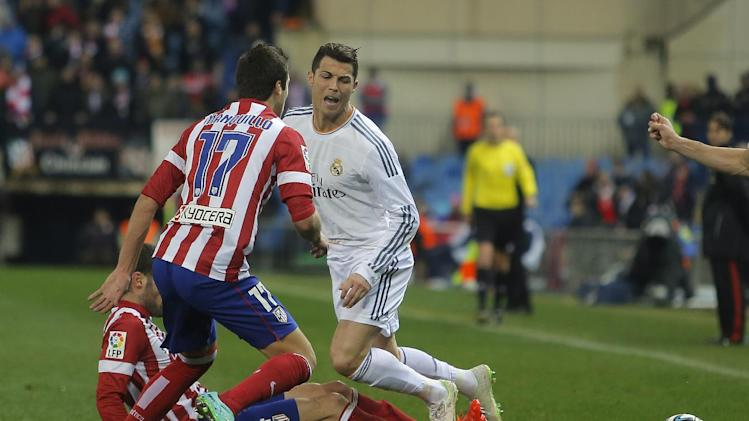 Real's Cristiano Ronaldo in action with Atletico's Mario Suarez, left, during a semi final, 2nd leg, Copa del Rey soccer match between Atletico de Madrid and Real Madrid at the Vicente Calderon stadium in Madrid, Spain, Tuesday, Feb. 11, 2014