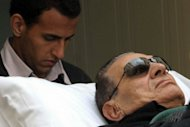 Ousted Egyptian President Hosni Mubarak is wheeled on a stretcher into court for his murder trial in Cairo in January 2012. Mubarak was declared clinically dead after he was transferred to hospital from prison on Tuesday, state media reported, but a medical source said he was in a coma