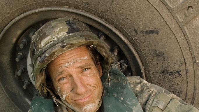 Mike's 100th Dirty Jobs Special: Host Mike Rowe poses against the muddy truck tire of the extracted army truck.