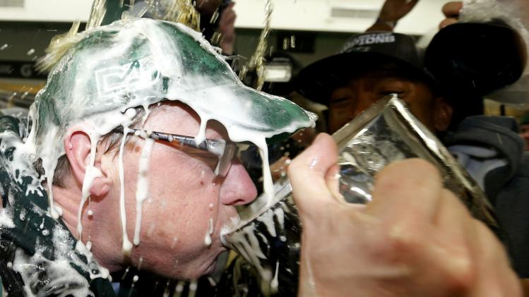 Saskatchewan Premier Wall sips out of the Grey Cup as beer is poured over him in the locker room after the Saskatchewan Roughriders defeated the Hamilton Tiger-Cats to win the CFL's 101st Grey Cup championship football game in Regina