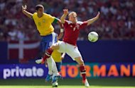 Brazil's midfielder Anderson Hernanes (L) and Denmark's striker Michael Krohn-Dehli jump for the ball during the international friendly football match at the Imtech Arena stadium in Hamburg. A young Brazil side stepped up their preparations for the London Olympics by beating Denmark 3-1